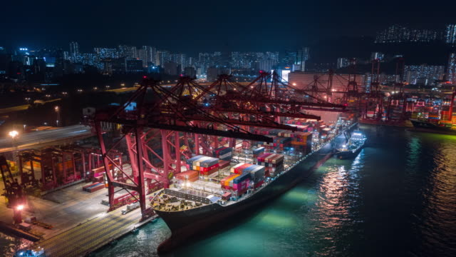 4k time lapse or hyper lapse : aerial view container cargo warehouse at terminal commercial port and working crane bridge loading container to container ship at night for business logistics, import export, shipping or transportation - freight elevator stock videos & royalty-free footage