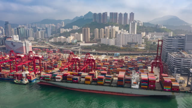4k time lapse or hyper lapse : aerial view container ship at terminal commercial port or container warehouse with hong kong cityscape for business logistics, import export, shipping or transportation - freight elevator stock videos & royalty-free footage