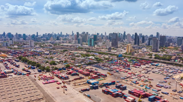 stockvideo's en b-roll-footage met 4k time lapse of hyper lapse : aerial view container warehouse bij terminal commercial port with cityscape and wonderful cloud for shipment business logistics, import export, shipping or transportation. - vrachtwagentransport