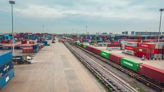 stockvideo's en b-roll-footage met 4k time lapse of hyper lapse : druk verkeer in container cargo warehouse bij terminal commercial port met mobile crane truck laadcontainer naar de freight train, business logistics import export of freight transportation. - lossen