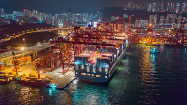 4k time lapse or hyper lapse : container cargo ship at terminal commercial port or container warehouse with hong kong cityscape at night for business logistics, import export, shipping or transportation. - unloading stock videos & royalty-free footage
