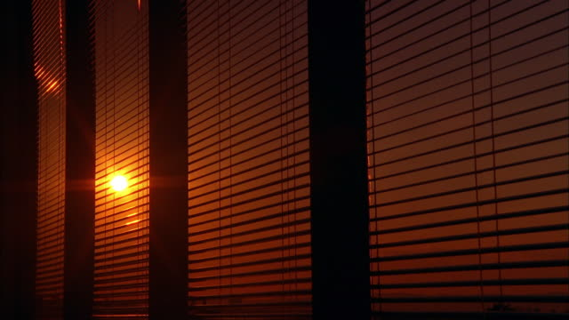 time lapse orange sun setting through blinds in office window - tapparella video stock e b–roll