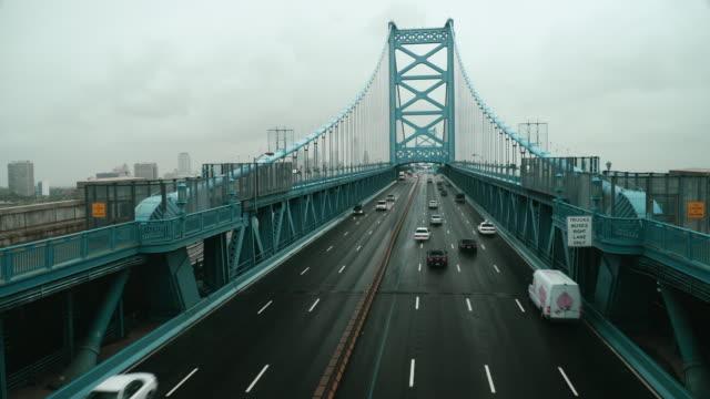 time lapse, overhead traffic crosses ben franklin bridge during rain storm. - ベンフランクリン橋点の映像素材/bロール