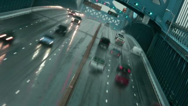Time lapse, overhead traffic crosses Ben Franklin Bridge during rain storm.
