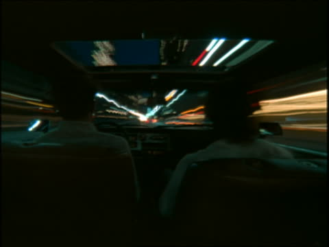 vídeos y material grabado en eventos de stock de time lapse over-the-shoulder of driver + passenger car point of view in traffic on city street at night / los angeles, california - 1985