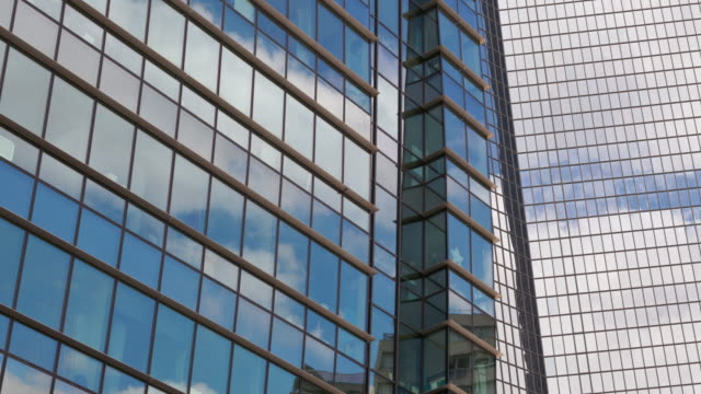 vidéos et rushes de time lapse pan of clouds on office buildings in business district la defense paris - en verre
