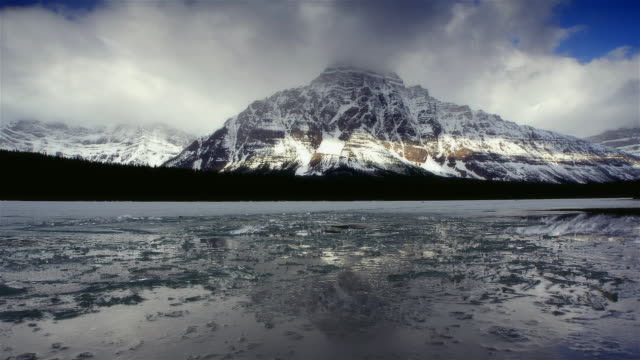 time lapse panning frozen body of water with snow-covered mountain along banks - frozen water stock videos & royalty-free footage