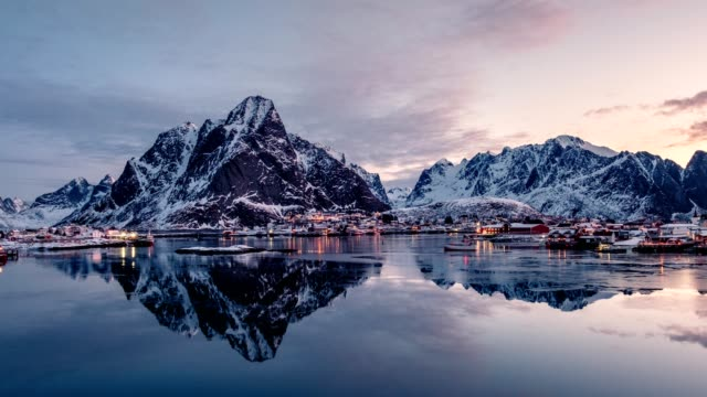 Time lapse panning of Norwegian fishing village surrounded with mountains in morning