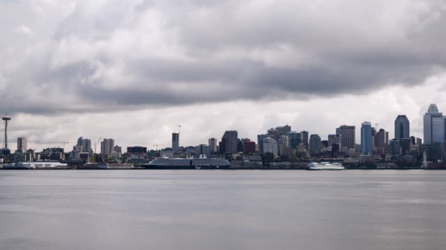 w/s time lapse panning through the seattle skyline with elliott bay in the foreground on a mostly cloudy day with dark gray low clouds - elliott bay bildbanksvideor och videomaterial från bakom kulisserna