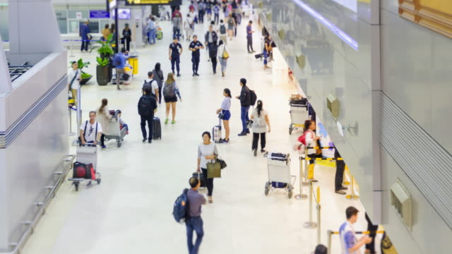 4k time lapse :passengers and world travelers check in at airport.zoom out styles. - airline check in attendant stock videos and b-roll footage