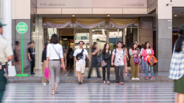 time lapse: pedestrian crowd at walkway in front of building entrance - daytime