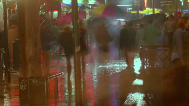 time lapse pedestrian traffic on Leicester Square in the rain at night / London, England
