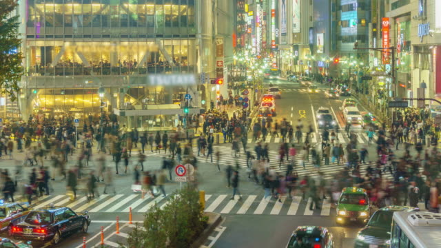 Time lapse: Pedestrians cross at Shibuya Crossing in Tokyo , Japan .