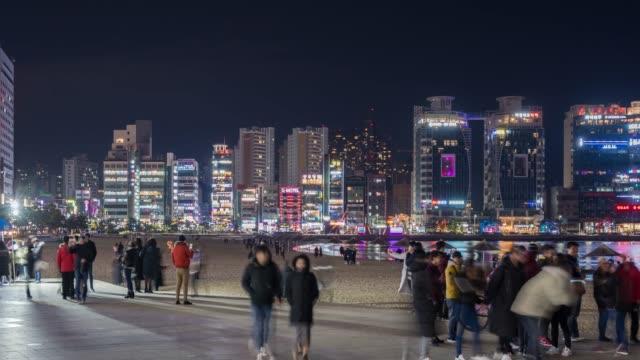 4k time lapse : pedestrians tourist walking at gwangalli beach in busan city, south korea - busan stock videos & royalty-free footage