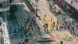 Time lapse people and taxi cabs crossing a very busy crossroads in Tsim Sha Tsui district Hong Kong, China