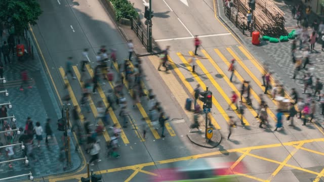 vídeos de stock e filmes b-roll de time lapse people and taxi cabs crossing a very busy crossroads in tsim sha tsui district hong kong in china - parte mediana