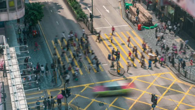 time lapse people and taxi cabs crossing a very busy crossroads in tsim sha tsui district hong kong, china - tsim sha tsui stock videos & royalty-free footage