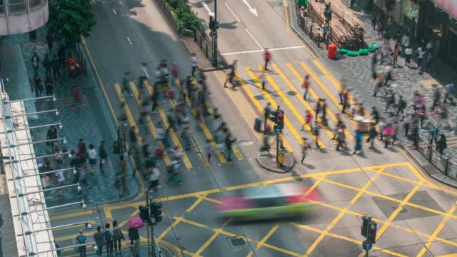 zeitraffer-personen und taxis, die eine sehr belebte kreuzung im tsim sha tsui bezirk hong kong in china überqueren - berg victoria peak stock-videos und b-roll-filmmaterial