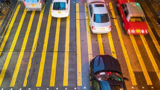 vídeos de stock, filmes e b-roll de pessoas com lapso de tempo e táxis atravessando uma encruzilhada muito movimentada no distrito de mong kok em hong kong, na china - mong kok