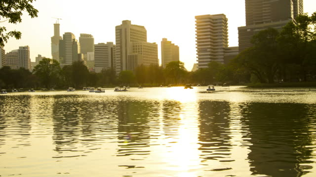 stockvideo's en b-roll-footage met time lapse : people enjoy relaxing on boat in the park from day to sunset - waterfiets
