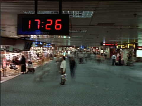 time lapse people in airport terminal / digital clock in foreground - digital clock stock videos and b-roll footage