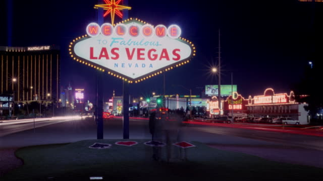 Time lapse people taking pictures in front of the the 'Welcome to Fabulous Las Vegas, Nevada' sign at night