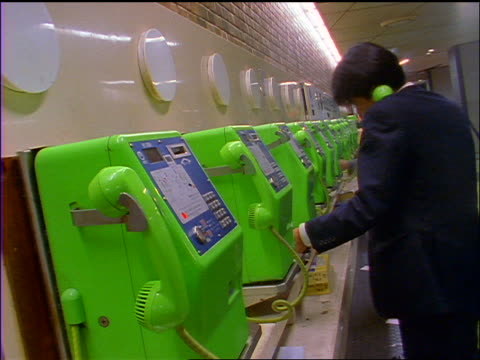 time lapse people using green pay phones indoors / Shibuya Station, Tokyo