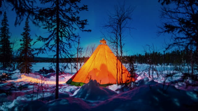 Time Lapse: People Walking in and Out of a Lit Up Teepee at Night