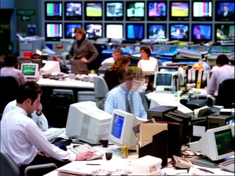 archival time lapse - cu people working in television news room, banks of tv screens in background - press room stock videos & royalty-free footage