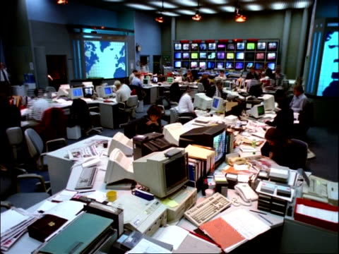 archival time lapse - ms people working in television news room, banks of tv screens in background - press room stock videos & royalty-free footage