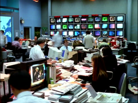 ARCHIVAL Time lapse - CU People working in Television News Room, banks of TV screens in background