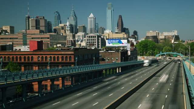 Time lapse, Philadelphia cityscape, commuter traffic races across Ben Franklin Bridge.