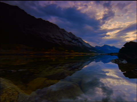 time lapse point of view over mountain lake surface reflecting clouds + Rockies at dusk / Jasper Nat'l Park, Alberta