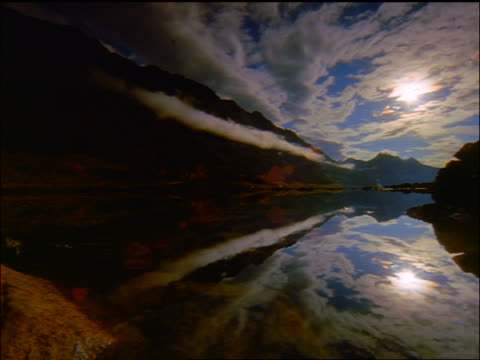 time lapse point of view over mountain lake surface reflecting storm clouds + Canadian Rockies / Alberta