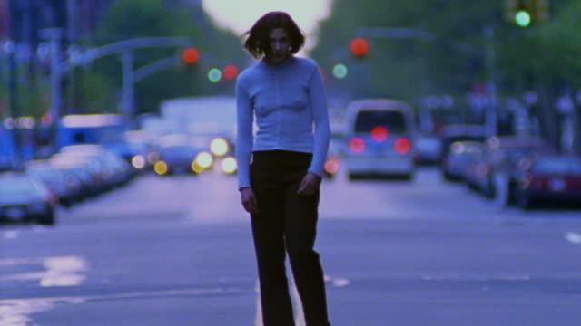 time lapse PORTRAIT woman standing in middle of street with traffic in background / New York City