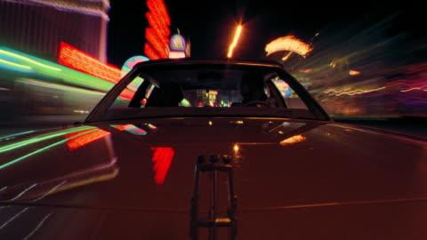 vídeos y material grabado en eventos de stock de time lapse rear car point of view driving through las vegas at night with blurred neon lit buildings / nevada, usa - letrero de neón
