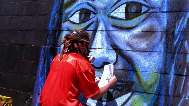 MS time lapse REAR VIEW young man with dreadlocks spraypainting mural of face (self portrait) on wall / low angle