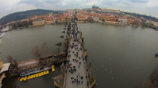 time lapse recorded from above the charles bridge of prague with cityscape and crowd of tourist people walking visiting the city in winter with cloudy day. - charles bridge stock videos and b-roll footage
