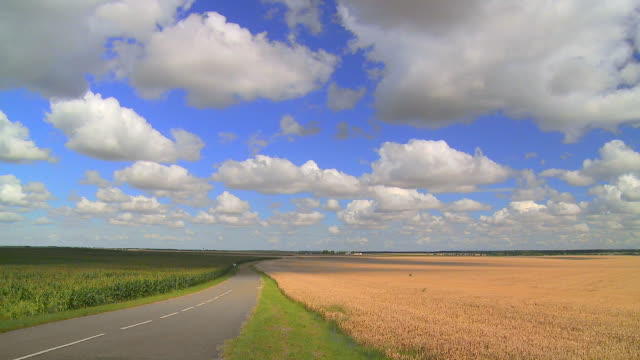 time lapse road, fields, blue sky with white clouds - stationary stock videos & royalty-free footage