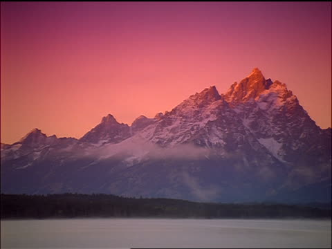 time lapse PAN rocky Grand Teton mountains with mist on Jackson Lake in foreground / sunrise