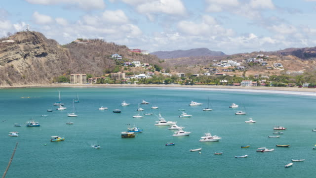 time lapse san juan del sur. coast line from an aerial point of view. we can see the fisher boats on the blue pacific sea and the jesus statue on the left top. sunny day with some clouds that shade the landscape. - nicaragua stock videos and b-roll footage