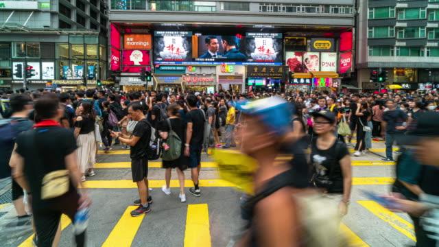 4k zeitraffer szene der menge unkenntlich, dassimprotestierer, die um tsim sha tsui herumlaufen, hong kong - central bezirk hongkong stock-videos und b-roll-filmmaterial