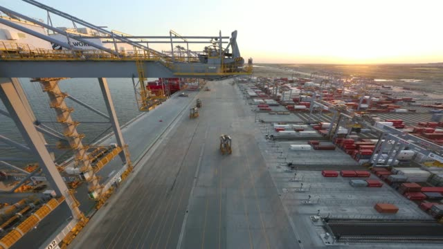 vídeos de stock, filmes e b-roll de a time lapse sequence at dusk shows high angle view of straddle carriers moving freight containers past ship to shore cranes during loading... - moving activity