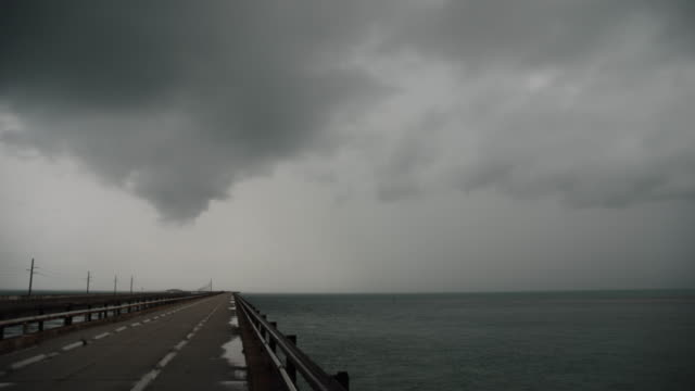 Time lapse sequence of a thunderstorms ominous dark clouds moving from left to right past the Seven Mile Bridge in Marathon FL