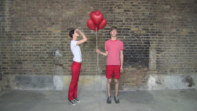 vídeos de stock, filmes e b-roll de time lapse sequence of boy holding heart shaped balloons, girl entering scene and bursting the balloons before they both walk off - corpo inteiro