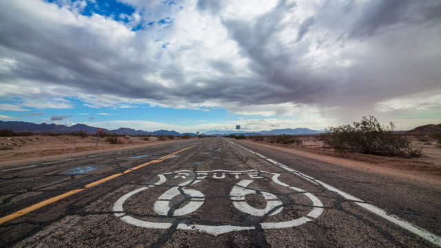vidéos et rushes de time lapse sequence of clouds drifting over the famous route 66 highway. - route 66