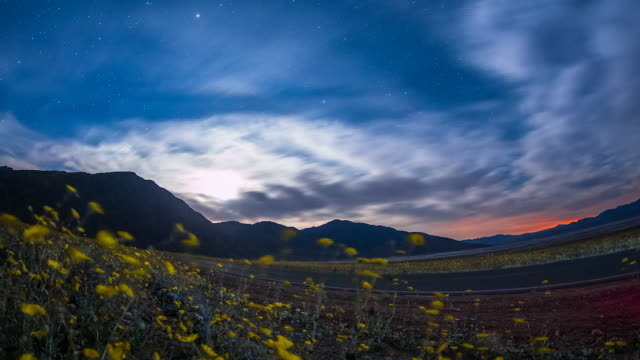 vídeos de stock e filmes b-roll de time lapse sequence showing clouds and stars moving over death valley, california. - data