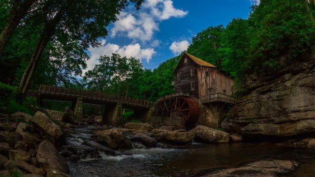 time lapse sequence showing the changing of the seasons near a water mill in the new river gorge national park. - le quattro stagioni video stock e b–roll