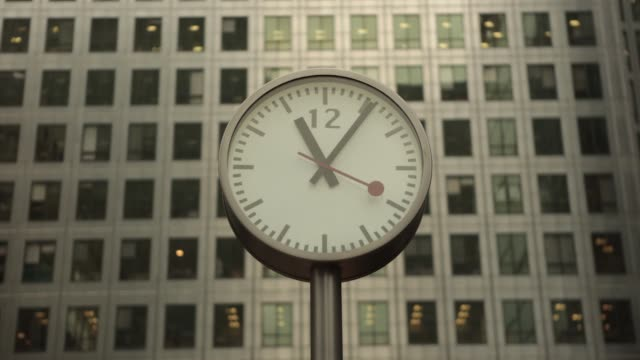 time lapse sequence shows clockface with time at one o'clock in the afternoon in canada square time lapse sequence shows pedestrians and commuters... - clock stock videos & royalty-free footage