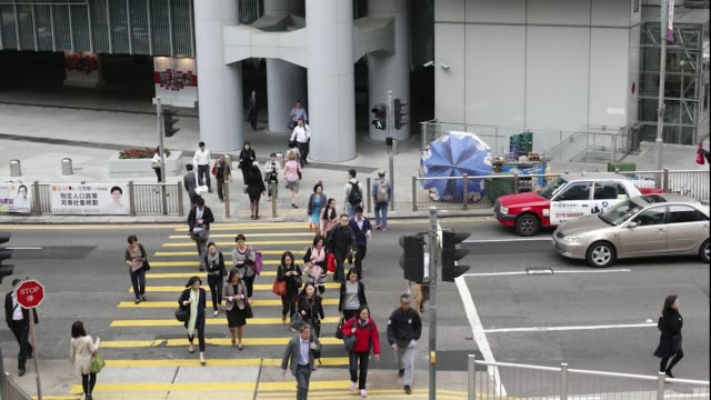 stockvideo's en b-roll-footage met time lapse sequence shows high angle view of commuters crossing a street outside the hsbc building in the central district of hong kong china on... - hongkong eiland